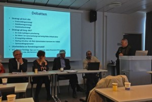 Det er 4 personer ved et bord, foran et lerret som viser en agenda. Møteleder står til høyre.