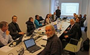 Bilde fra møte med Svensk eDelegation. Vi ser personer rundt et bord, og en som foreleser ved lerretet